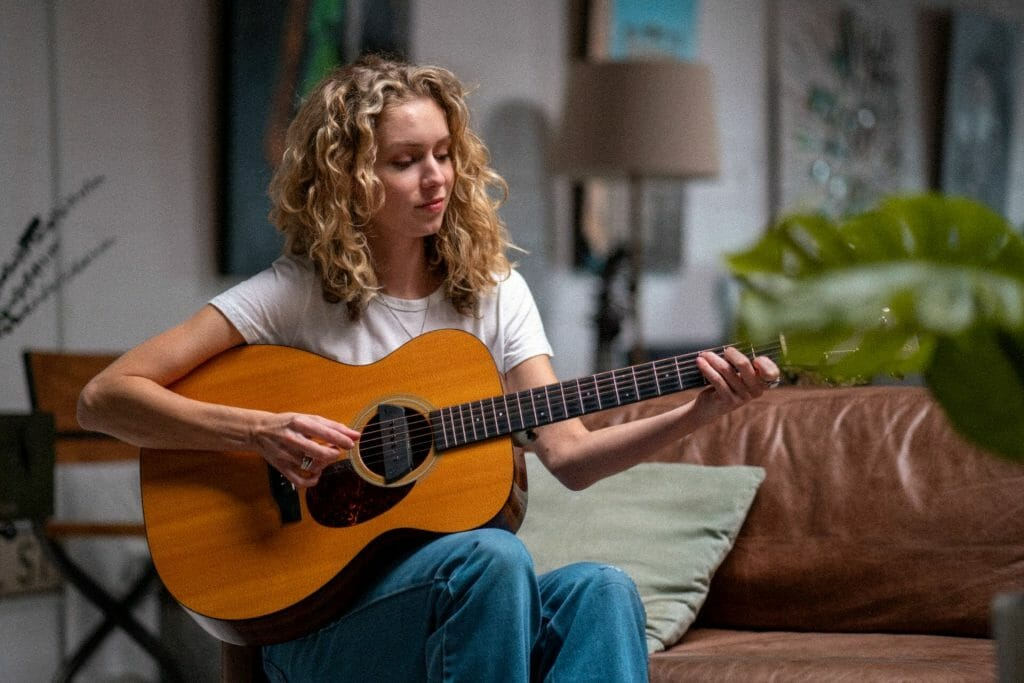 woman playing guitar when bored