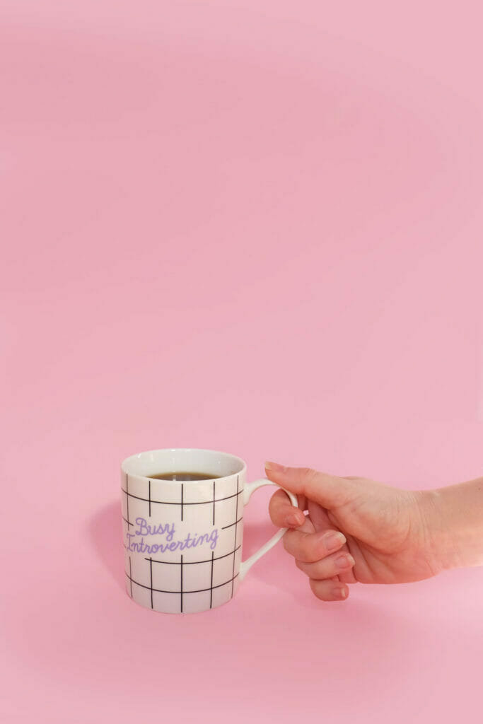 hand holding mug that says busy introverting