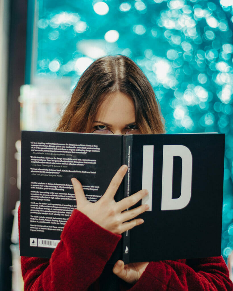 girl holding up a book in front of face