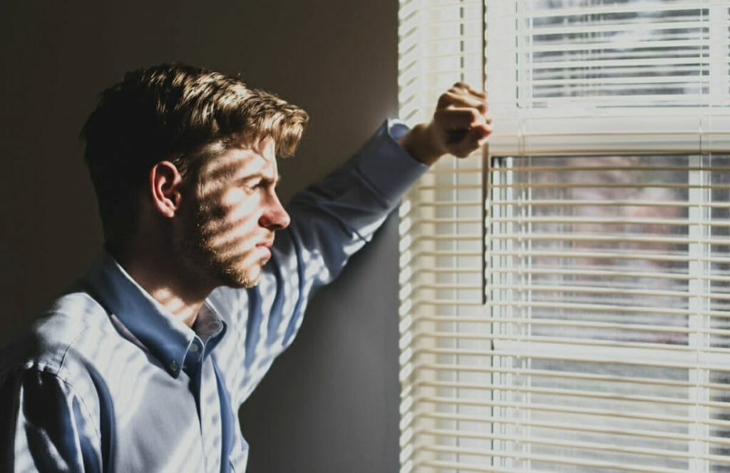 man looking out window sadly